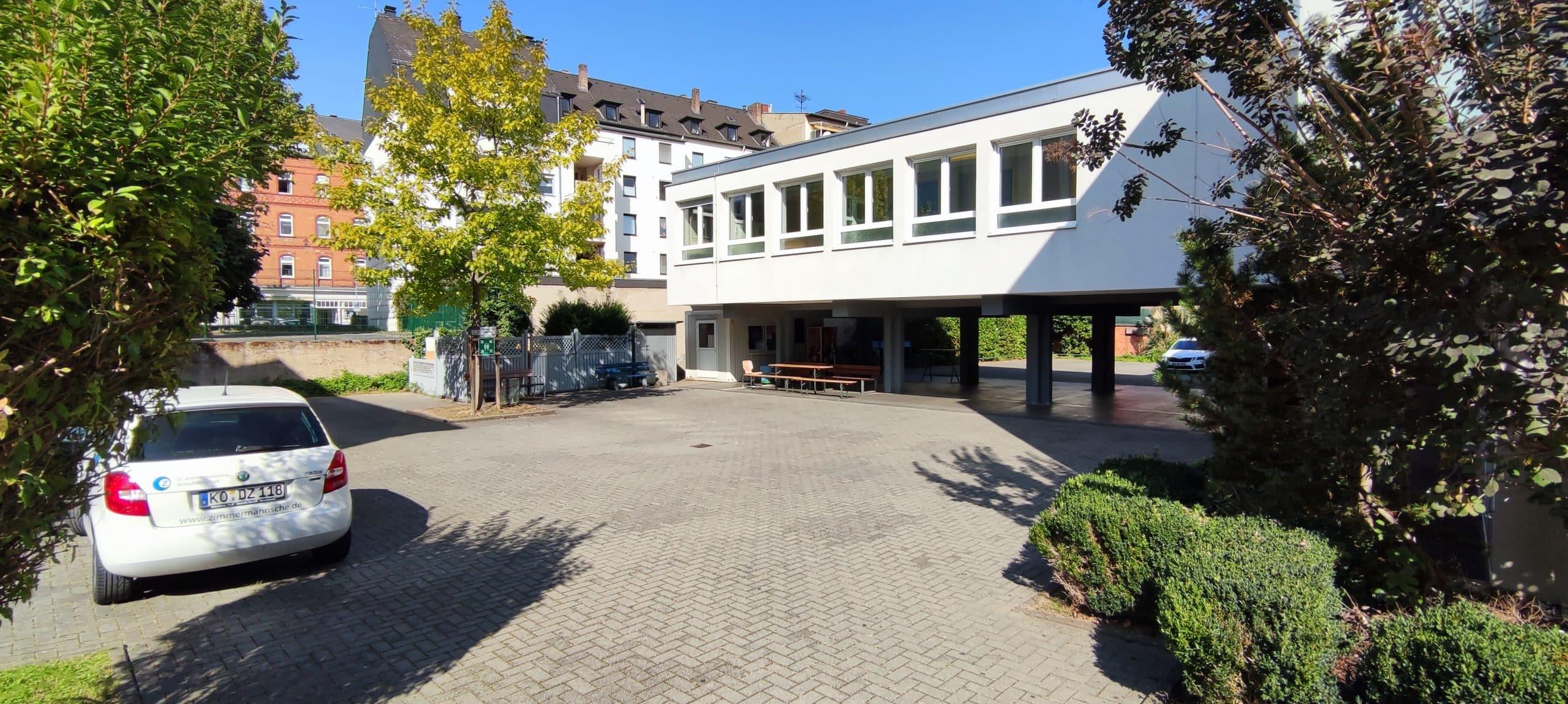 Dr. Zimmermannsche Wirtschaftsschule in Koblenz Schulhof aus Sicht der Hofeinfahrt mit Blick auf Firmenfahrzeug und den Anbau